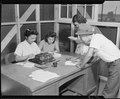 Granada Relocation Center, Amache, Colorado. A temporary timekeeping office is a busy spot as the f . . . - NARA - 538737.tif