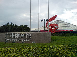 "An outer view of indoor stadium/complex with conical roof, greenery in front, and an inscription – ""Guangzhou Gymnasium"" in both English and Chinese."