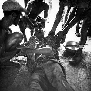 Franco-Vietnamesen behandeln einen verwundeten nordvietnamesischen Gefangenen nach einer Schlacht