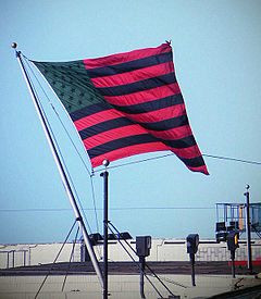 The flagstaff is set atop the building, tilted 45° to the left, and the flag is rippling in the wind to the right.