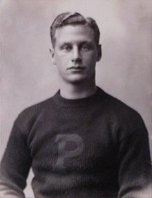 "Black-and-white photo of the upper half of a young man wearing a sweater with a large ""P"" on the front"