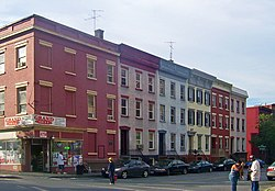 "A row of four three-story flat-roofed brick buildings in various colors seen from across a corner. There are people standing on the other corners. The building nearest the camera, at the left, has a a sign at street level saying ""Grand Deli"" and another, smaller one saying ""ATM""."