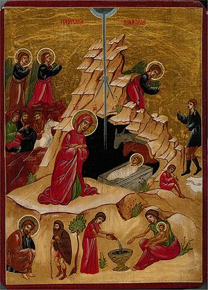 Badnjak (Serbian) - The icon of the Nativity. The Theotokos and the Christ Child, who lies in the manger in the cave, are at the center. Two shepherds are on the right, one of them sitting and playing music for his flock.