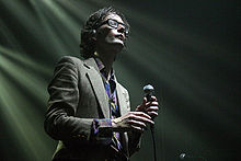 Jarvis Cocker—a Caucasian man with brown hair wearing glasses and a suit—holds a microphone onstage with his eyes closed.