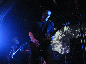 Post-metal - Justin Broadrick performing with Jesu at Roadburn Festival 2012, with visual art in the background. The aesthetic of post-metal often accentuates artistic expression over conventional heavy metal fashion.