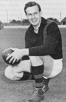 A dark-haired footballer in a long-sleeve black guernsey with a diagonal sash and white shorts squatting while holding a football
