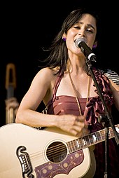 A woman in a purple dress singing to a microphone and playing the guitar.