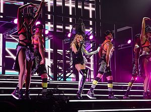 "Get Outta My Way - Minogue, surrounded by dancers, performing ""Get Outta My Way"" during her Kiss Me Once Tour (2014)."