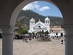 View through an arch onto a paved square with a fountain in the center and a white church on the far side