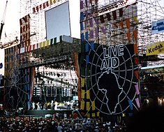 "An outdoor stage with the a banner bearing the words ""Live Aid"" above an image of Afiica and a large audience many raising their hands"