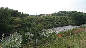 Clydebridge Steelworks - View across the river Clyde of the site of Auchenshuggle Bridge in 2008 - the buildings of Clydebridge are behind the trees on the left and the spoil mound can be seen rising on the right