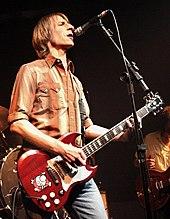 Um guitarrista do sexo masculino e cantor, Mark Arm, é no palco, segurando uma guitarra elétrica.