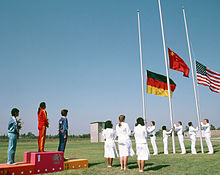 On a grassed outdoor field, three women stand on a podium to the left of the shot, while people wearing all white raise three flags on flagpoles situated at the right of shot.