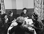 Members of the Women's Auxiliary Air Force (WAAF) enjoy a meal at a RAF base in Britain during 1942. D6851.jpg