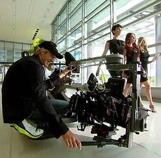 Michael Bay - Bay filming Transformers: Age of Extinction; actresses Abigail Klein, Melanie Specht and Victoria Summer are walking in a corridor.