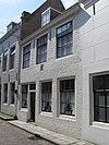 Huis met geverfde rechte gevel met gootlijst op klossen