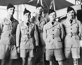 Five men in light-coloured military uniforms with dark forage caps