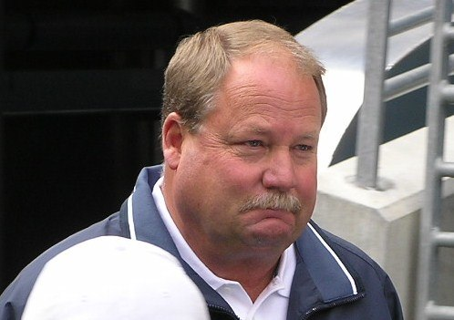 Candid head and shoulders photograph of Holmgren wearing a green jacket over a white shirt