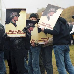 Color image of protesters in late 20th century clothing holding signs showing a soldier in Wehrmacht uniform