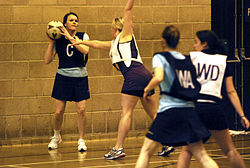 Female netball player in dark bib holding the ball with her hands positioned to make a two handed pass. She is being guarded by another female player in a white bib.