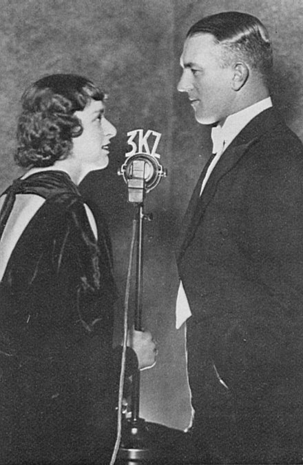 "Naomi (""Joan"") Melwit and Norman Banks at the 3KZ microphone, in the late 1930s. Norman Banks Naomi Melwit 3KZ.jpg"