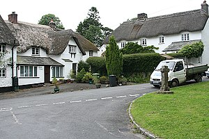 North Bovey - The village green at North Bovey showing thatched cottages and the stone cross