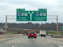 Traffic flows down a four-lane Interstate highway underneath a large sign indicating traffic exits