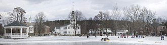Norwich, Vermont - Panoramic view of Norwich in winter. Left to right are: bandstand, Tracy Hall (town hall), Norwich Congregational Church, private residences, and the Marion Cross (elementary) School. In the foreground is a seasonal skating area.