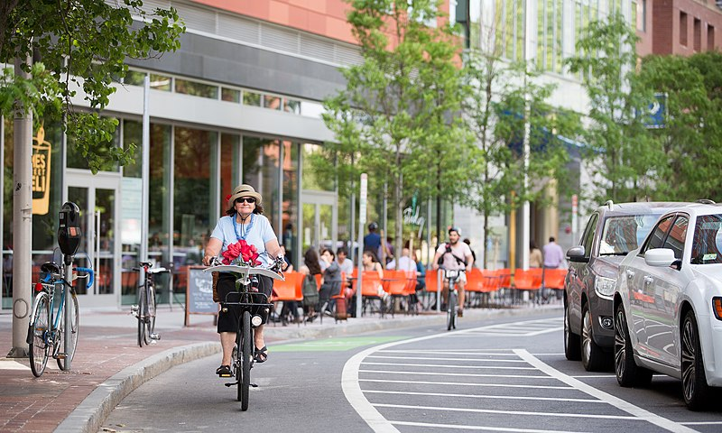 File:Older woman with flowers protected bike lane boston.jpg