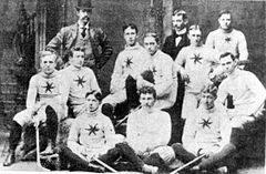 Ten men, wearing white team uniforms, in two rows across the picture, each holding a hockey stick. Behind them are two men, team executives, standing in their suits, one wearing a bowler hat.