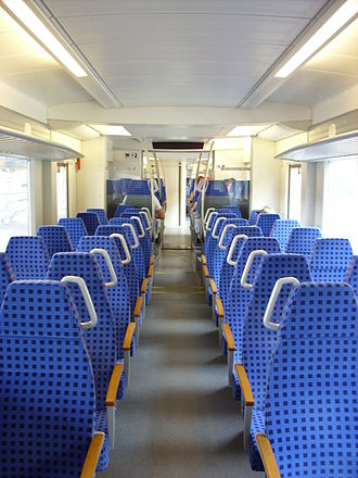 Standing passenger - Grab rails on a longer-distance commuter train which is designed mostly for seated passengers