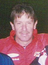 Smiling middle-aged white man wearing a red anorak