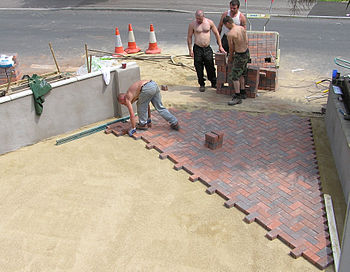 Brick paving being laid on a sand base, in sou...