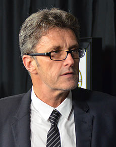 Bespectacled man in a grey suit. This is a photo of Paweł Pawlikowski in 2015.