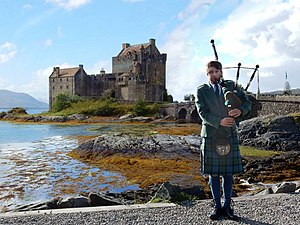 Piper at Eilean Donan Castle, Scotland.JPG