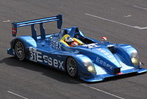A view of a bright blue race car with the word Essex clear to read on the side