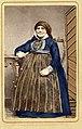 Porträtt av sittande kvinna iklädd sockendräkt som vilar armen på bord i nyrokoko. Herrestad i Skåne - Nordiska Museet - NMA.0042848.jpg