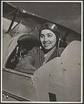 Portrait of Begum Haroom wearing flying cap in the cockpit of a biplane, ca. 1953 (16102403990).jpg