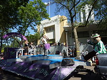 "Young woman standing on a purple float, behind a sign that says ""Princess Kay of the Milky Way"". Float is passing the Horticulture building. Fairchild, the fair's mascot, is at right."