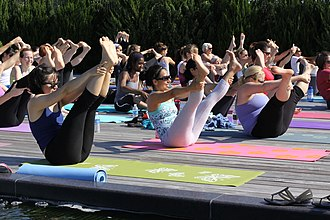 Yoga for therapeutic purposes - An outdoor yoga session. The participants are practising Navasana, boat pose.