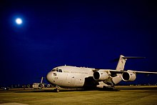 Four-engined military jet transport plane parked on airfield at night with moon overhead