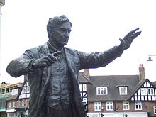 Outdoor statue of middle-aged man with raised arms as if conducting an orchestra