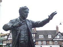 Уличная статуя мужчины средних лет с поднятыми руками, будто дирижирует оркестром