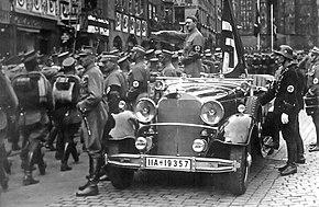 Photo noir et blanc prise en septembre 1935. Dans une rue de Nuremberg, Adolf Hitler, debout à l'arrière d'une voiture au premier plan, salue des troupes de miliciens de la SA défilant sur sa gauche. On distingue aussi, à l'arrière de la voiture, juste derrière Hitler, le drapeau à croix gammée de cérémonie, Blutfahne, et, en uniforme SS, debout à droite, devant la portière de la voiture, Jakob Grimminger, porteur officiel du Blutfahne.