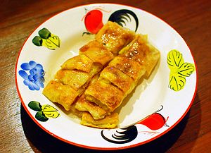 "Roti - A Thai ""โรตีกล้วยไข่ /rɒtiː klûaj kʰàj/"": roti with banana and egg, drizzled with sweetened condensed milk"