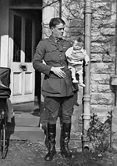 Informal full-length portrait of man in military uniform holding an infant