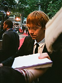 A picture of a man with red hair looking downward. A person is extending their arm to whist holding sheets of paper. Trees and red heights can be seen in the background.