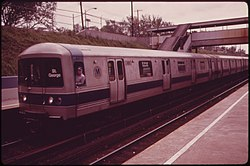 A Staten Island Railway train composed R44 subway cars on the Staten Island Railway. This image, taken in 1973, shows the cars with a since-removed blue stripe toward the bottom of the car body. The train is arriving at a platform to the left; the photo is taken from another platform to the right and in the foreground. The station is in a right-of-way below street level, and a covered footbridge connecting the two platforms is located to the right.