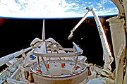 "A shuttle in space, with Earth in the background. A mechanical arm labelled ""Canada"" rises from the shuttle"