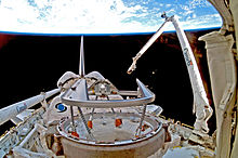 "A Space Shuttle in space, with Earth in the background. A mechanical arm labelled ""Canada"" rises from the Shuttle."
